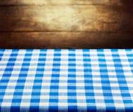 Nappe bleue à carreaux au-dessus de fond en bois Photographie stock libre de droits
