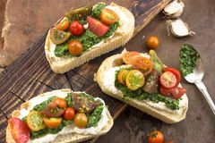Appetizer bruschetta with chopped vegetables, Mascarpone and pesto sauce on ciabatta . rustic weathered wood background Stock Images