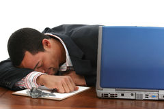 Napping businessman. Businessman with his head resting on his arm on a desktop, with his eyes closed and a smile on his face Stock Photography