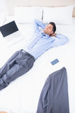 Napping businessman lying on his bed Stock Photo
