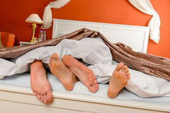 Napping couple barefoot lying under covers bed Stock Photography