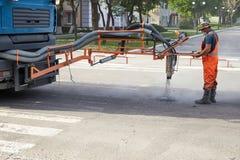 Naprawa asfaltowe jamy, dmucha gorącą miksturę bitum i gruz zdjęcia stock