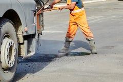 Naprawa asfaltowe jamy, dmucha gorącą miksturę bitum i gruz obraz royalty free