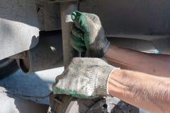 Naprawa samochodowy zawieszenie gloved ręka Zamieniać szoka absorberu dumnego kroka fotografia stock