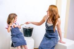 Naprawa w mieszkaniu Szczęśliwa rodziny matka, córka w fartuchach i przygotowywaliśmy malować ścianę z białą farbą Siedzi z muśni obraz stock