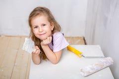 Naprawa w mieszkaniu Szczęśliwej rodziny macierzysta i mała córka w błękitnych fartuchach maluje ścianę z białą farbą Dziewczyna  fotografia stock