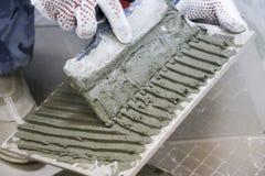 Naprawa - wewnętrzna dekoracja Kłaść podłogowe ceramiczne płytki Mężczyzna ` s ręk kaflarz w rękawiczkach z szpachelki rozszerzan obrazy stock