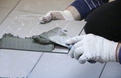 Naprawa - wewnętrzna dekoracja Kłaść podłogowe ceramiczne płytki Mężczyzna ` s ręk kaflarz w rękawiczkach z szpachelki rozszerzan zdjęcia royalty free