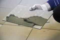 Naprawa - wewnętrzna dekoracja Kłaść podłogowe ceramiczne płytki Mężczyzna ` s ręk kaflarz w rękawiczkach z szpachelki rozszerzan fotografia stock