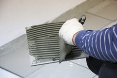 Naprawa - wewnętrzna dekoracja Kłaść podłogowe ceramiczne płytki Mężczyzna ` s ręk kaflarz w rękawiczkach z szpachelki rozszerzan zdjęcie royalty free