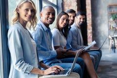 Naprawdę dobra informacja Grupa młodzi ludzie siedzi na konferenci i ono uśmiecha się wpólnie obrazy royalty free