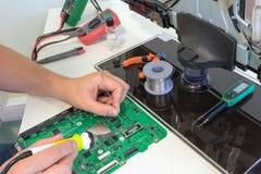 Naprawia dowodzone TV części w usługowym centrum, lutuje elektronicznych składniki Obrazy Royalty Free