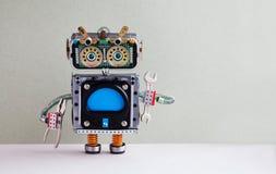 Naprawianie komputeru pojęcie Mechaniczni złotej rączki ręki wyrwania cążki Kolorowa pokazu robota zabawka, pusty błękitny monito zdjęcie royalty free
