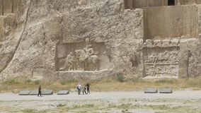 Naqsh-e Rustam Relief. NAQSH-E RUSTAM, IRAN - MAY 3, 2015: Tourist sightseeing ancient relief of the necropolis Naqsh-e Rustam that shows the triumph of Shapur I stock video footage