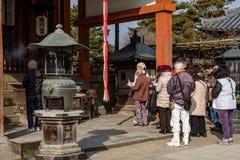 NARA, JAPÃO - 30 DE JANEIRO DE 2018: Povo japonês que reza no templo de Nara imagem de stock royalty free