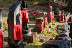 NARA, JAPAN - JAN 30, 2018: Stone Buddha sculptures wearing red clothes in temple of Nara from side stock image