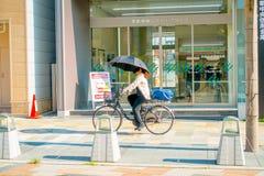 Nara Japan - Juli 26, 2017: Den oidentifierade kvinnan som cyklar på gatorna och, besöker ett shoppa område i Nara, Japan Nara är Arkivbilder