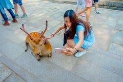 Nara Japan - Juli 26, 2017: Stäng sig upp av den oidentifierade kvinnan som tar en selfie av en lös hjort i Nara, Japan Nara är a Royaltyfri Bild