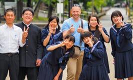 Nara Japan - Maj 14: Fotografen Pierre Aden poserar med japanska stundents för ett foto på Maj 14, 2014 i Naha, Japan Arkivfoto