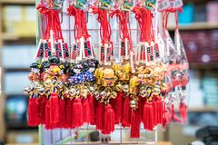 Nara Prefecture, Japan - 2 Mar 2018: Japanese amulet with bell; girl in blue and red yukata, gold cat, deer hang on to white grill. Nara Prefecture, Japan - 2 stock photos
