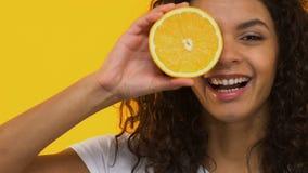 Naranja alegre de la tenencia de la muchacha, vitaminas y nutrición sana, concepto del skincare almacen de metraje de vídeo