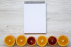 Naranja anaranjada y siciliana Agrios con la libreta en blanco en el fondo de madera blanco, desde arriba Endecha plana imágenes de archivo libres de regalías