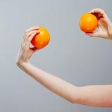 Naranja china en la mano asiática de la mujer en fondo concreto gris Fotografía de archivo