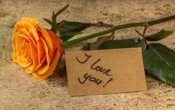 Naranja color de rosa y nota te amo sobre el papel del arte imagen de archivo libre de regalías