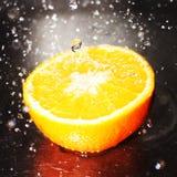 Naranja con el chapoteo del agua Imágenes de archivo libres de regalías