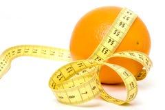 Naranja con la cinta de medición imagenes de archivo
