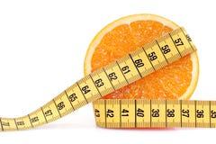 Naranja con la cinta métrica Fotos de archivo