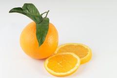 Naranja con las hojas y las rebanadas Imagenes de archivo