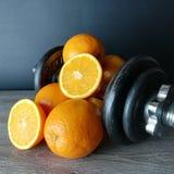 Naranja con los pesos, la salud y la aptitud imagen de archivo