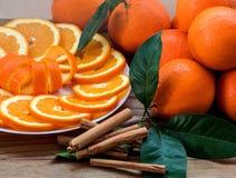 Naranja cortada con ánimo espiral en la placa y el groupe de naranjas en la tabla de madera foto de archivo