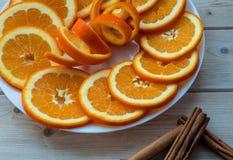 Naranja cortada con ánimo espiral en los palillos de la placa y de canela en la tabla de madera fotografía de archivo libre de regalías