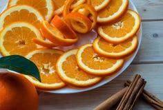 Naranja cortada con ánimo espiral en los palillos de la placa y de canela en la tabla de madera fotografía de archivo