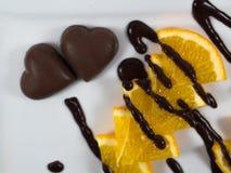 Naranja cortada con los caramelos de chocolate en blanco Fotografía de archivo libre de regalías