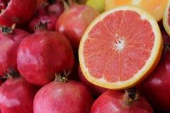 Naranja de sangre a medias roja en una pila de granadas en el mercado fotos de archivo