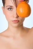 Naranja del asimiento de la muchacha de la belleza de Yung delante del ojo Imagen de archivo libre de regalías