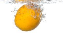 Naranja en agua con las burbujas Imágenes de archivo libres de regalías