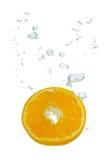 Naranja en agua con las burbujas de aire fotos de archivo