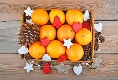 Naranja en bandeja wickered con la decoración de la Navidad Fotografía de archivo
