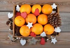 Naranja en bandeja wickered con la decoración de la Navidad Fotos de archivo