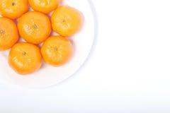 Naranja en el plato blanco Fotos de archivo