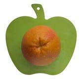 Naranja en forma de la manzana que talla al tablero Imagen de archivo