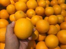 Naranja en la mano izquierda y el fondo imagen de archivo libre de regalías