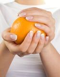 Naranja en las manos de la mujer Imágenes de archivo libres de regalías