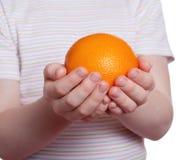 Naranja en las palmas del niño Foto de archivo libre de regalías
