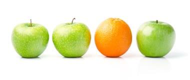 Naranja entre manzanas verdes Fotos de archivo libres de regalías