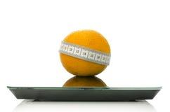 Naranja envuelta con la cinta métrica en una escala Foto de archivo libre de regalías